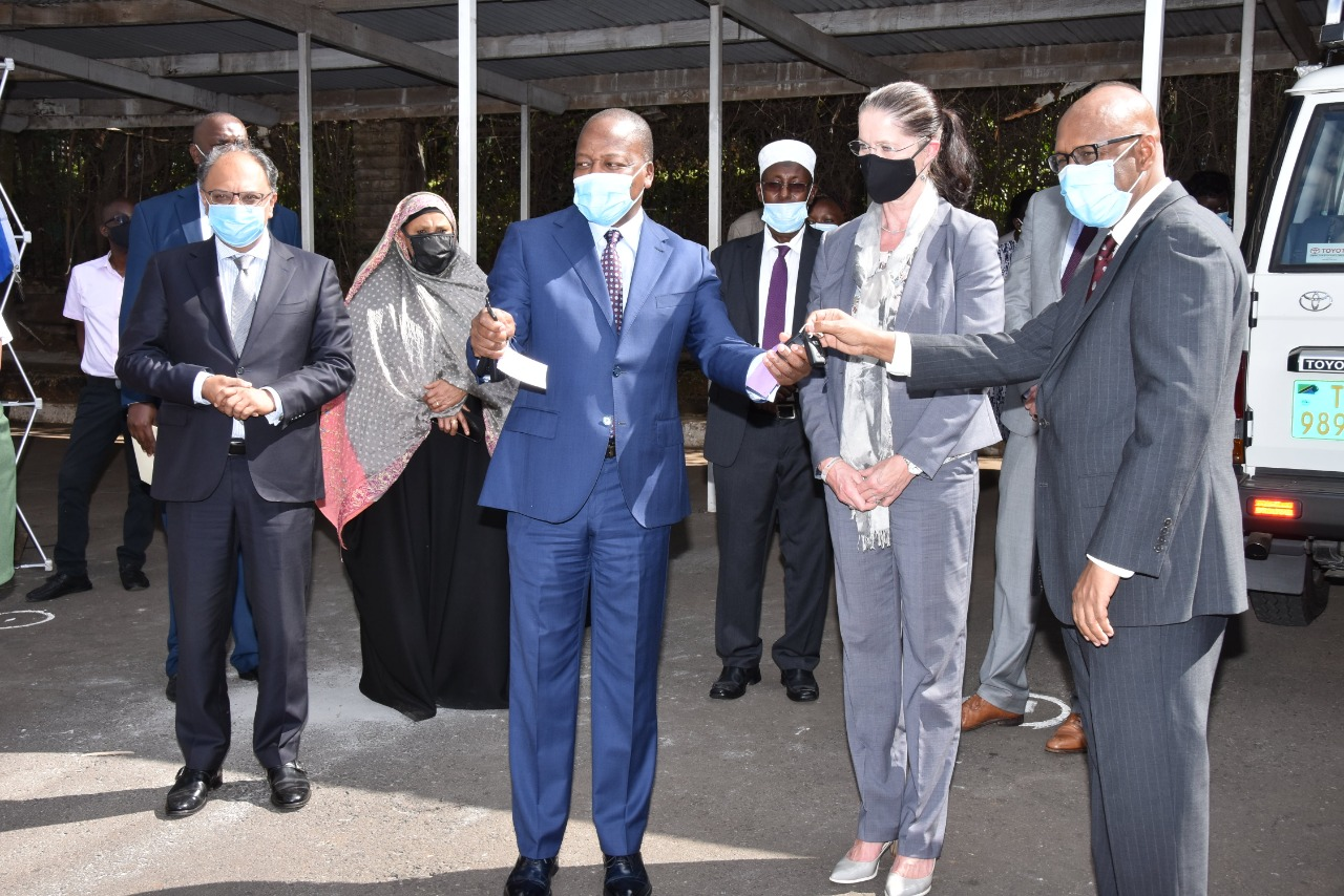 Kenya's Cabinet Secretary for Health, Hon. Mutahi Kagwe (left), receives car keys for the two EAC Mobile Labs from his EAC Affairs counterpart, Mr. Adan Mohammed. Looking on (centre) is German Ambassador to Kenya, Ms. Annett Gunther.