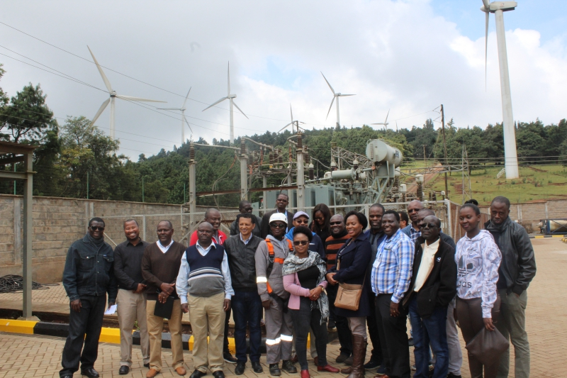 Communication experts from the RECs, Journalists, and Energy Experts in a group photo opportunity with the Electrical Engineer in charge of the Wind Farm, Eng. Kaarinah Luvango