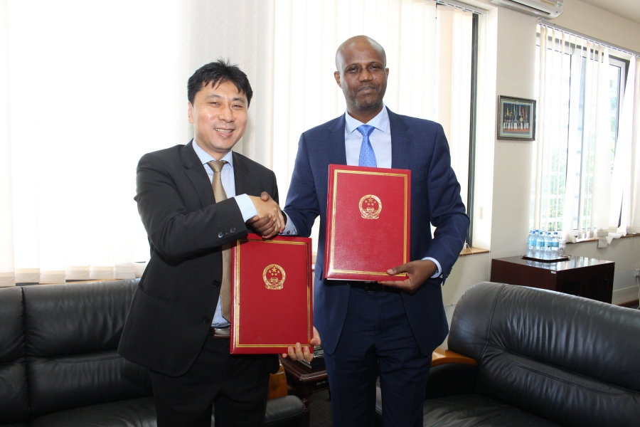 The Political Counselor at the Chinese Embassy in Dar es Salaam, Mr. Liang Lin, exchanging particulars with the EAC Secretary General Amb. Liberat Mfumukeko after the two signed the framework agreement under which China has granted EAC US$200,000 to support various capacity building programmes.